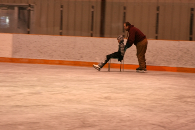 Jonathan enjoying a ride from Dad on the ice rink